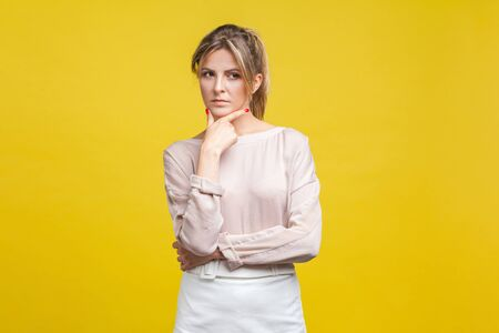 Portrait of thoughtful serious young woman with blonde hair in casual beige blouse standing, holding her chin and thinking over solution, doubts. indoor studio shot isolated on yellow background
