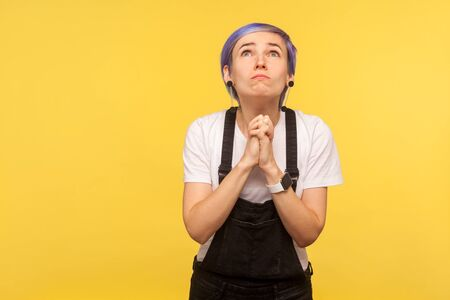 Please, I'm begging! Portrait of hipster woman with violet short hair in denim overalls looking up pleadingly and holding hands in prayer, begging forgiveness. indoor, yellow background, studio shot