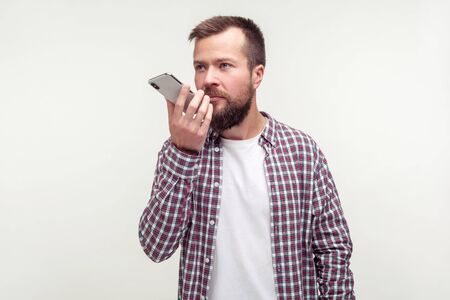 Portrait of serious bearded man in casual plaid shirt talking to mobile phone using voice application, audio message or recorder. indoor studio shot isolated on white background