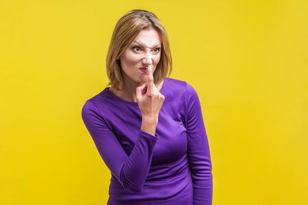 Portrait of angry young woman in tight purple dress looking aside and pointing at her nose, saying to trickster you are liar, body language. indoor studio shot isolated on yellow background Stockfoto