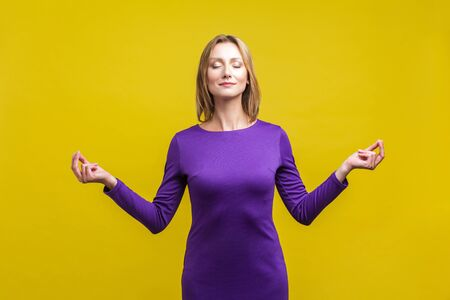 Yoga practice, harmony. Portrait of peaceful woman in purple dress standing with closed eyes and calm face meditating, holding fingers in mudra gesture. studio shot isolated on yellow background