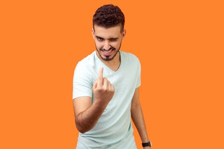 Come here! Portrait of handsome brunette man with flirtatious smile in casual white t-shirt winking and making beckoning gesture, inviting to approach. indoor studio shot isolated on orange background