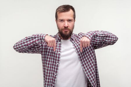 Look down, here and right now! Portrait of bossy strict bearded man in casual plaid shirt pointing fingers down and looking seriously at camera. indoor studio shot isolated on white background