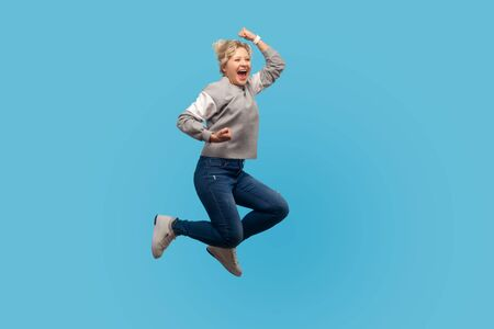 Portrait of enthusiastic happy woman with short curly hair in sweatshirt jumping in air showing yes i did it gesture, life energy and freedom concept. indoor studio shot isolated on blue background Stock fotó