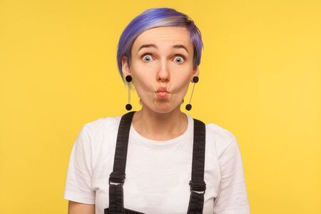 Portrait of amusing hipster girl with violet short hair in denim overalls making fish face with goofy comical expression, silly grimace, having fun. indoor isolated on yellow background, studio shot Stock fotó