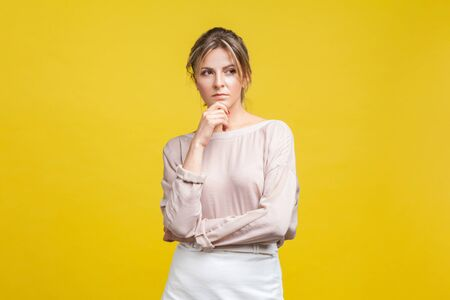 Portrait of pensive or confused young woman with blonde hair in casual beige blouse standing, holding her chin and thinking over problem solution. indoor studio shot isolated on yellow background Stock fotó
