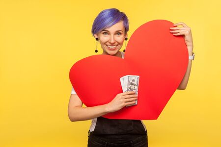 Money and love. Portrait of smiling positive hipster girl with violet short hair in denim overalls holding big paper heart and bunch of dollars. isolated on yellow background, indoor studio shot