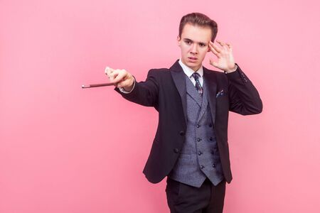 Portrait of concentrated focused magician in tuxedo touching temple with fingers and raising magic wand, using mental power to perform trick, illusionist show. studio shot isolated on pink background