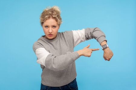 Look at time! Displeased impatient woman with curly hair in sweatshirt pointing at wrist watch, anxious about delay, saying its late hour, hurry up. indoor studio shot isolated on blue background