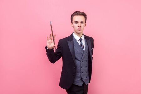 Portrait of young magician in tuxedo standing with raised magic wand and looking at camera with serious focused expression, illusionist showing trick. indoor studio shot isolated on pink background