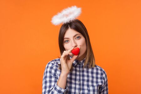 Portrait of playful angelic woman with brown hair wearing checkered shirt, standing with halo on head, kissing toy heart and looking at camera. indoor studio shot isolated on orange background