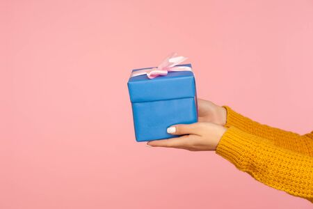 Closeup of woman hands in sweater holding wrapped blue gift box, arms giving birthday present to side, holiday celebration, copy space for advertise. indoor studio shot isolated on pink background