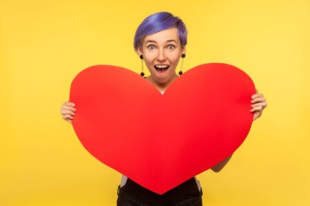 Romantic feelings. Portrait of surprised hipster girl with violet short hair in overalls holding big paper heart and looking with amazed eyes, valentines day. isolated on yellow background studio shot