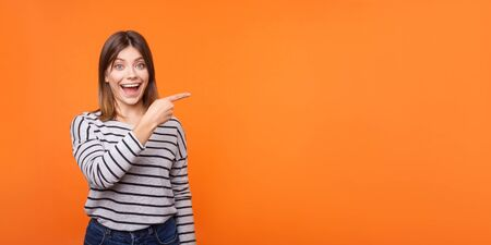 Portrait of amazed happy young woman with brown hair in long sleeve striped shirt standing, pointing at copy space wall for advertise information. indoor studio shot isolated on orange background