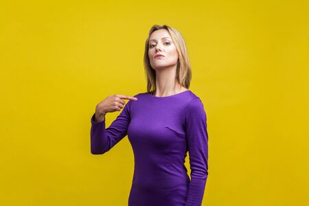 This is me! Portrait of arrogant businesswoman in tight elegant purple dress pointing at herself, looking egoistic and haughty, proud of achievement. indoor studio shot isolated on yellow background