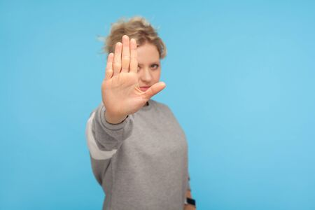 Denial, rejection concept. Young woman with short hair in sweatshirt showing stop gesture, no sign with raised palm, warning about prohibition, limit. indoor studio shot isolated on blue background