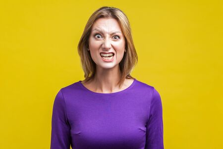 Portrait of beautiful emotional woman in tight purple dress standing with clenched teeth and angry grimace on face, pretending to be aggressive. indoor studio shot isolated on yellow background
