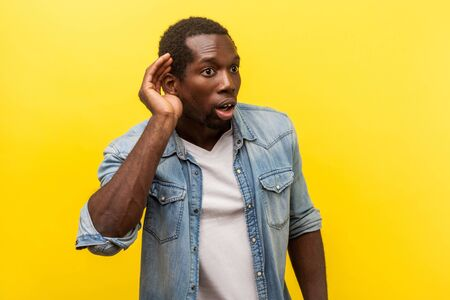Portrait of attentive surprised man in denim casual shirt with rolled up sleeves putting hand to ear to hear better, listening carefully to rumors. indoor studio shot isolated on yellow background Stock Photo
