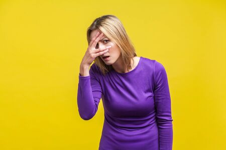 Portrait of curious young woman in elegant tight purple dress standing looking through fingers with prying eyes, spying with cunning face expression. indoor studio shot isolated on yellow background Stock Photo