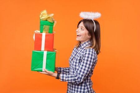 Side view portrait of lovely angelic brunette woman in checkered shirt standing with halo on head, holding gift boxes and smiling, holiday presents. indoor studio shot isolated on orange background