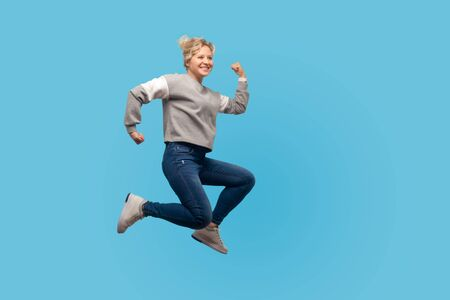 Full length portrait of woman with short hair in sweatshirt and jeans jumping or running in air, looking energetic and joyful, rushing for weekends. indoor studio shot isolated on blue background