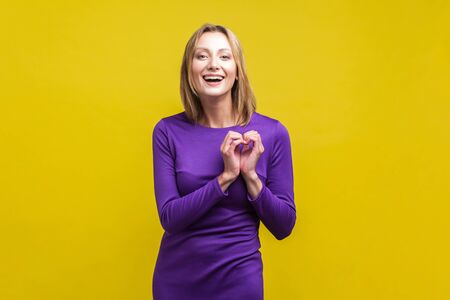 Love, romantic feelings. Portrait of cheerful young woman in elegant tight purple dress showing heart symbol with fingers and smiling at camera. indoor studio shot isolated on yellow background