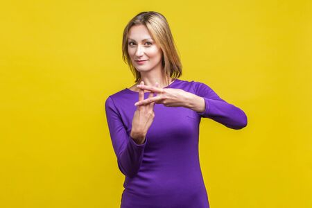 Hashtag gesture. Portrait of beautiful cheerful woman in elegant tight purple dress showing hash symbol with crossed fingers, looking at camera. indoor studio shot isolated on yellow background