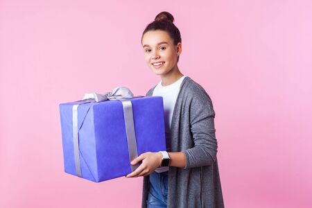 Holiday present and bonuses. Portrait of cheerful teenage brunette girl with bun hairstyle in casual clothes holding gift box and and smiling at camera. indoor studio shot isolated on pink background