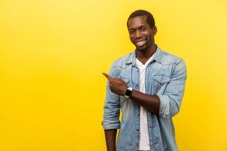 Schauen Sie, werben Sie hier! Porträt eines positiven Mannes in lässigem Jeanshemd, das auf die linke Seite zeigt und in die Kamera lächelt und leeren Raum für Werbung zeigt. Indoor-Studioaufnahme isoliert auf gelbem Hintergrund