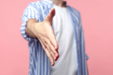 Closeup of male hand outstretched for greeting, man in casual striped shirt giving arm to handshake, welcoming at job interview, business deal. indoor studio shot isolated on pink background