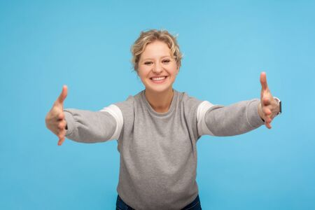Free hugs, come here! Happy kind hearted woman with curly hair in sweatshirt opening her hands wide to give warm welcome, friendly hospitable smile. indoor studio shot isolated on blue background Stock fotó