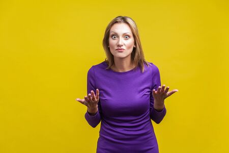 How could you? Portrait of disappointed unhappy woman in elegant tight purple dress standing with raised hands asking what do you want, angry face. indoor studio shot isolated on yellow background Stock Photo