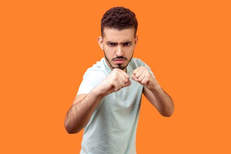 Boxing and self-defence. Portrait of weak angry brunette man with beard in casual white t-shirt frowning and keeping fists clenched, ready to defend in fight. studio shot isolated on orange background