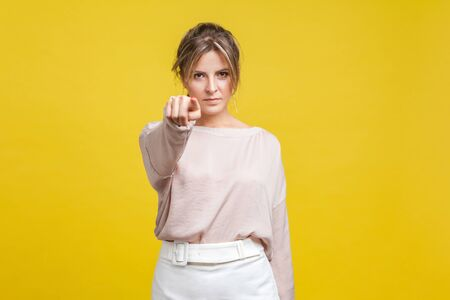 Portrait of serious bossy woman with blonde hair in casual beige blouse standing, looking at camera and pointing finger, blaming or criticizing. indoor studio shot isolated on yellow background