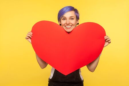 Portrait of romantic positive hipster girl with violet short hair in overalls holding big paper heart and smiling, sharing love feeling, valentines day. isolated on yellow background, studio shot