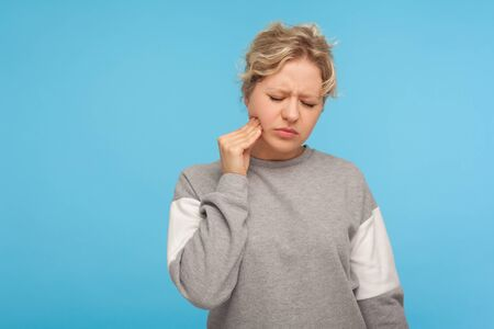 Portrait of unhappy adult woman with short curly hair in sweatshirt touching chin suffering tooth ache, jaw pain or dental injury, has sensitive teeth. indoor studio shot isolated on blue background Stok Fotoğraf