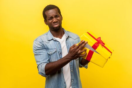 Portrait of unhappy man in denim casual shirt turning away from unpacked gift box with upset disappointed grimace, dissatisfied with bad present. indoor studio shot isolated on yellow background Stok Fotoğraf - 137678125