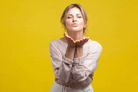 Portrait of happy in love beautiful woman with blonde hair in casual beige blouse standing, looking at camera and sending air kiss, romantic feelings. indoor studio shot isolated on yellow background Stock fotó