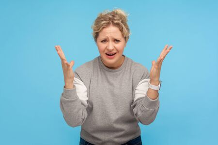 How could you? Displeased woman with short hair in casual sweatshirt raising hands in questioning gesture with indignant face, confused about reason, asking what. indoor studio shot blue background