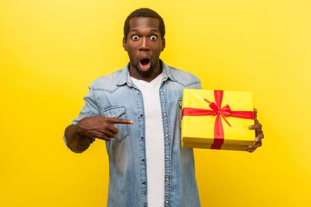Wow, amazing present! Portrait of shocked man in denim casual shirt looking at camera with open mouth and pointing at gift box, surprised with bonuses. indoor studio shot isolated on yellow background