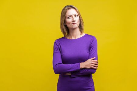 Portrait of perplexed thoughtful woman in tight purple dress standing with hands on her belly, looking aside with doubting inquiring expression. indoor studio shot isolated on yellow background