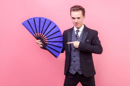 Portrait of young positive magician, man in elegant suit standing pointing at big blue fan, showing trick performance and looking with intriguing expression. studio shot isolated on pink background