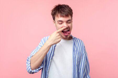 Porträt eines lustigen braunhaarigen Mannes mit kleinem Bart und Schnurrbart in lässigem Hemd, der seine Nase mit geschlossenen Augen und Zunge herauspickt, alberner Ausdruck. Indoor-Studioaufnahme auf rosa Hintergrund isoliert