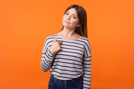 This is me! Portrait of proud young woman with brown hair in long sleeve striped shirt standing, pointing at herself, looking arrogant and selfish. indoor studio shot isolated on orange background