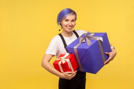 Portrait of admired joyful hipster girl with violet short hair in overalls holding two gifts, big and small holiday present boxes, looking at camera with toothy smile. yellow background, studio shot Imagens