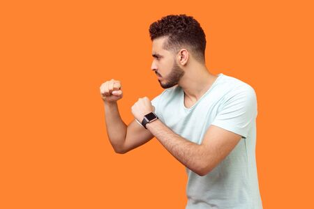 Boxing and self-defence. Side view of aggressive man with beard in white t-shirt keeping fists clenched, ready for fight. empty copy space on left for text. studio shot isolated on orange background