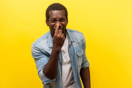 You are liar! Portrait of positive man in denim casual shirt with rolled up sleeves pointing at his nose showing lie gesture and laughing at camera. indoor studio shot isolated on yellow background Stockfoto