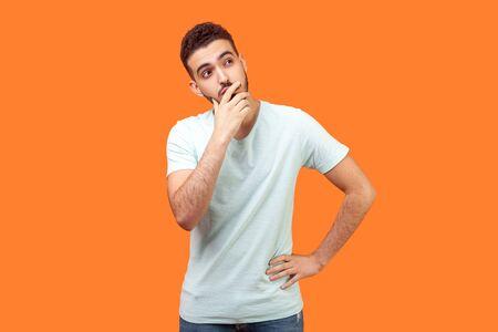 Necesidad de pensar. Retrato de hombre morena pensativo con barba en camiseta blanca sosteniendo su barbilla y reflexionando sobre la idea, confundido, no estoy seguro de la solución. Foto de estudio de interior aislado sobre fondo naranja Foto de archivo