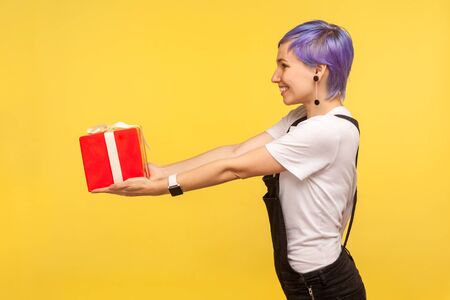 Take present! Side view portrait of happy trendy fashionable girl with violet short hair in overalls giving present box and smiling, holiday charity. indoor studio shot isolated on yellow background Stock Photo
