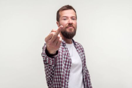 Portrait of impolite bully bearded man in casual plaid shirt showing middle finger fuck off gesture, aggressive hater expressing disrespect, protest. indoor studio shot isolated on white background